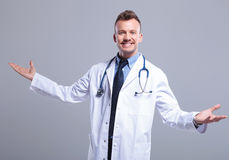Young smiling doctor welcoming you Stock Photos