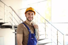 Young smiling electrician holding bunch of wires and standing. In light room Royalty Free Stock Photo