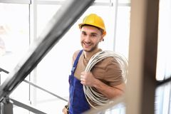 Young smiling electrician holding bunch of wires. In light room Royalty Free Stock Image