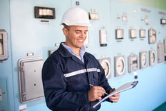 Young smiling engineer taking notes at control room Stock Photo