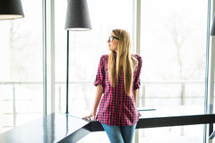 Young and smiling executive woman standing in front of the bright window Royalty Free Stock Image