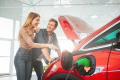 Young smiling family buying first electric car in the showroom. Attractive pleasantly surprised woman point at eco. Young smiling family buying first electric stock photography