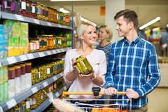 Young smiling family purchasing canned food for week. At supermarket Royalty Free Stock Photography