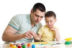 Young smiling father painting with son. Young smiling father painting with child son Royalty Free Stock Images