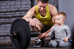 Young smiling father shows little son the dumbbell against brick wall at the cross fit gym.