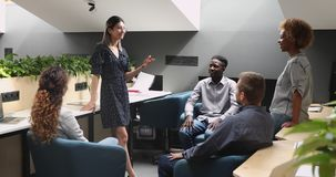 Smiling asian leader talking to multiethnic employees at office training. Young smiling female asian coach leader talking to multiethnic employees at office stock footage