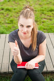 Young smiling female with book in the park show thumbup Royalty Free Stock Photos