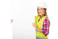 Young smiling female builder holding empty banner Stock Photo