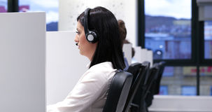 Female call centre operator doing her job. Young smiling female call centre operator doing her job with a headset Royalty Free Stock Photography