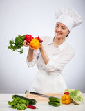 Young smiling female cook preparing salad Royalty Free Stock Photography