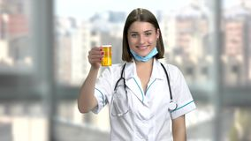 Young smiling female doctor with pills. Cheerful attractive young woman doctor holding a pill and showing thumbs up over blurred background stock footage
