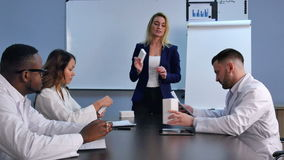 Young smiling female doctor presenting a white unlabeled box of pills stock video footage