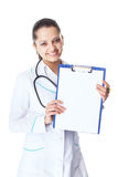 Young smiling female doctor showing blank clipboard Royalty Free Stock Images