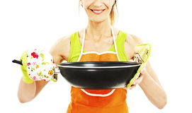 Young smiling female dressed in apron, holding a frying pan Royalty Free Stock Photo