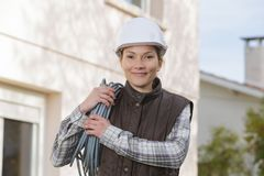 Young smiling female electrician outdoors. Female Stock Images
