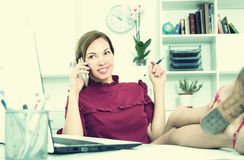 Young smiling female employee sitting relaxed with legs on worki Royalty Free Stock Photo