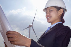 Young smiling female engineer holding open and looking down at blueprints, on site with wind turbines Stock Photography