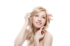 Young smiling female with flower in hair. Horizontal beauty portrait of young attractive caucasian blond smiling and gently locking female with pink lily flower stock photos