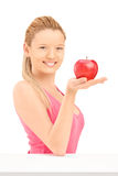 Young smiling female holding a red apple Stock Images