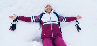 Young smiling female liying on the white snow wide opened her arms stock photography
