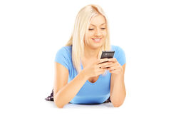 Young smiling female lying down and using her phone Royalty Free Stock Photo