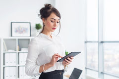 Young smiling female office worker at her workplace reading, browsing news ad messages using tablet computer while. Having break Royalty Free Stock Photo