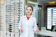 Young smiling female optician offering professional help in shop Royalty Free Stock Photo