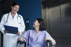 Young smiling female patient sitting in a wheelchair, looking up at the doctor standing beside her Stock Photos