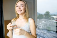 Young smiling female person drinking glass of water in morning at hotel. royalty free stock photos