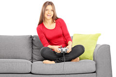 Young smiling female sitting on a couch and playing video game Royalty Free Stock Photography