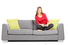 Young smiling female sitting on a sofa and playing video games Royalty Free Stock Photos