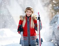 Female skier with skis on mountain. Young smiling female skier in ski center on mountain Royalty Free Stock Images