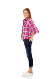Young smiling female standing with hands in pocket stock images