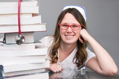 Young student  nurse with cap and books on table, smiling. Young smiling female student  nurse portrait wearing white scrubs, cap with tall pile of nursing Royalty Free Stock Photo