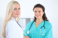 Young smiling female surgeon doctor standing at hospital. Medicine and health care concept.  Stock Photos