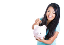 Young smiling female woman putting money in piggy bank savings Royalty Free Stock Photos