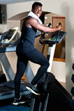 Young smiling fit african male burning calories. In the gym on an elliptical Royalty Free Stock Photo