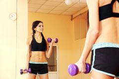 Young smiling fit woman doing exercises with dumbells Royalty Free Stock Photos