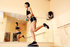 Young smiling fit woman doing exercises with dumbells on step board Royalty Free Stock Image