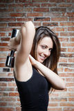 Young smiling fit woman lifting dumbbells Royalty Free Stock Photography