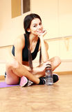 Young smiling fit woman resting on the floor with bottle of water Royalty Free Stock Photography