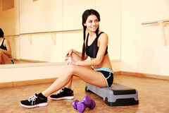 Young smiling fit woman sitting on the step board Stock Photos