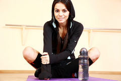 Young smiling fit woman sitting on the yoga mat Royalty Free Stock Photography