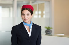 Young smiling flight assistant. Portrait of young air hostess standing at airport and looking at camera. Portrait of flight assistant in uniform standing near royalty free stock images