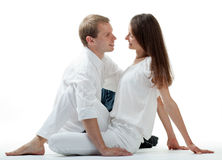 Young smiling flirting couple sitting on the floor Royalty Free Stock Photography