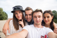 Young Smiling Friends Taking Selfie On Sandy Beach. A group of four young adult friends taking selfie on sandy beach stock photography