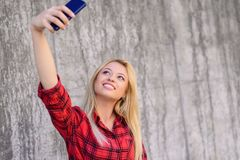 Young smiling girl with beautiful face taking self-portrait on her smartphone. She has blonde hair, beaming smile. She is wearing. Red checkered shirt. Close up royalty free stock photos