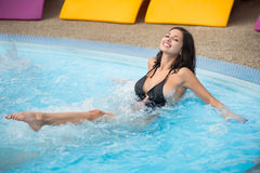 Young smiling girl in a black swimsuit in a swimming pool enjoying in jacuzzi Royalty Free Stock Photo