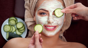 Young smiling girl with cosmetic mask at spa salon Royalty Free Stock Images