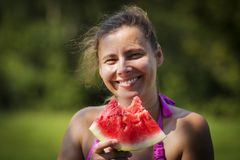 Young smiling girl eating watermelon. Woman with a piece of watermelon in outdoor. royalty free stock photo